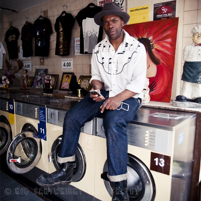 portrait man hat texting shirt laundrette washing machines broadway market hackney london streettogs street photography environmental portraiture rob cartwright