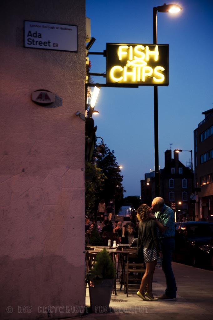 street photography streettogs night evening summer kiss love lovers romantic fish & chips shop broadway maket atmospheric artificial light hackney east london rob cartwright